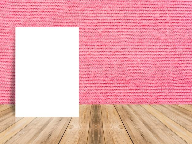 赤い布の壁と熱帯の木のテーブルの上にもたれて空白の白いポスター。 Premium写真