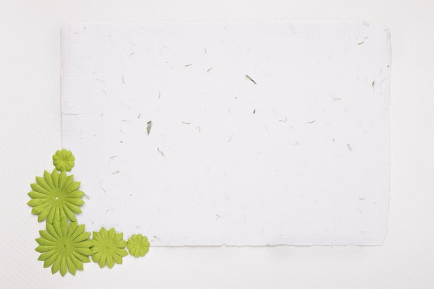 Blank white textured paper decorated with green flowers against background Free Photo