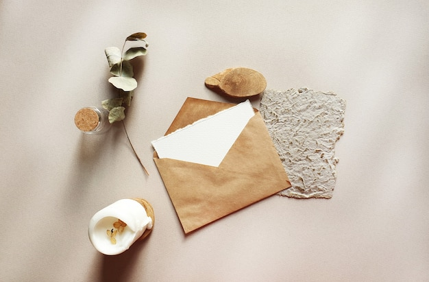 Blank white wedding greeting invitation cards mockups with craft envelope, dried eucalyptus leaves on textured table backgound. elegant modern template for branding identity. flat lay, top view Premium Photo