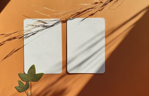 Blank white wedding greeting invitation cards mockups with dried leaves of plants and herbs on textured terracotta table backgound. elegant modern template for branding identity. flat lay, top view Premium Photo