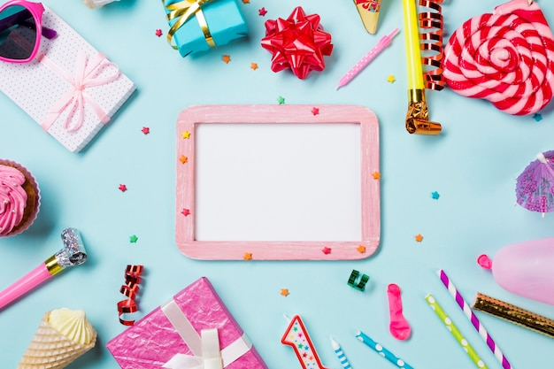 Blank white wooden frame decorated with birthday items on blue background Free Photo