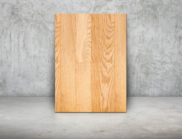 Blank wood block frame leaning at grunge grey concrete wall and floor Premium Photo