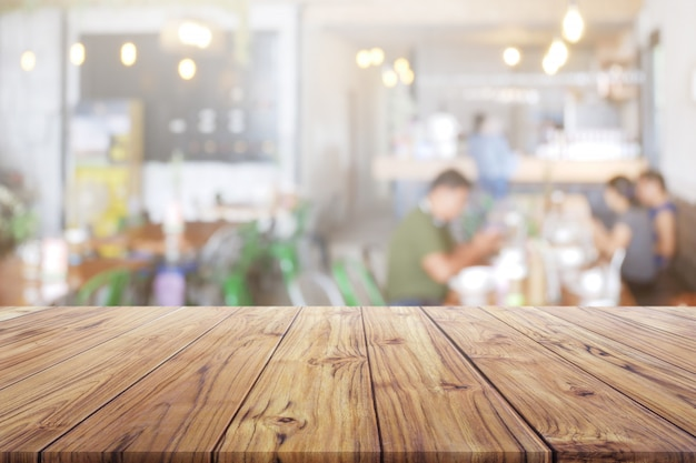 Blank wood table top with people at restaurant or coffee cafe background for montage product Premium Photo
