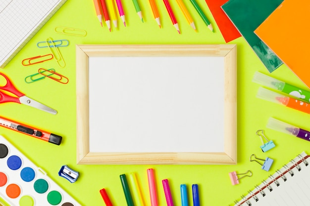Blank wooden frame and school supplies Free Photo