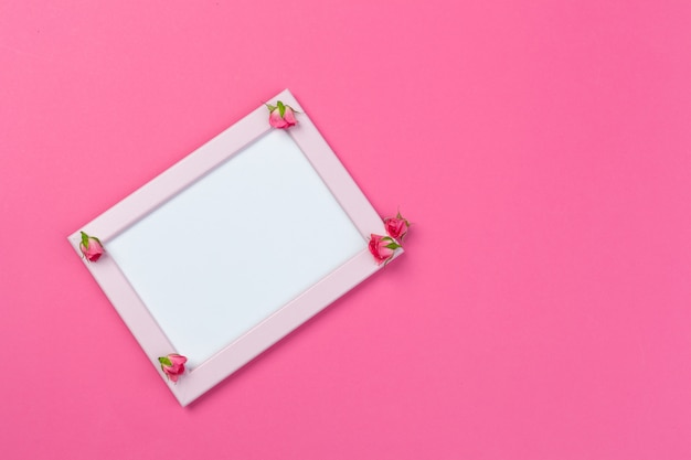 Blank wooden frame with flower blossoms on pink Premium Photo