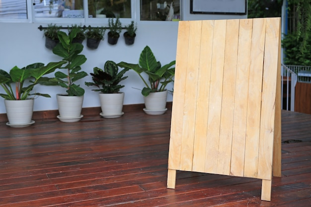 Blank wooden menu blackboard on floor in front of restaurant. Premium Photo