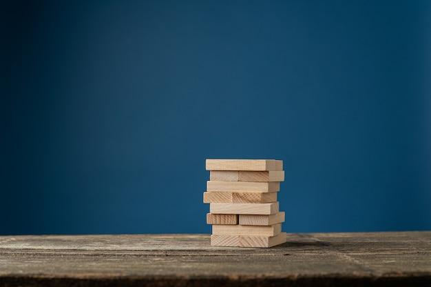 Пустые деревянные колышки сложены на деревенском деревянном столе в концептуальном изображении. на синем фоне. Premium Фотографии