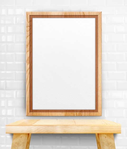 Blank wooden photo frame hanging at white tile wall on wood table. Premium Photo