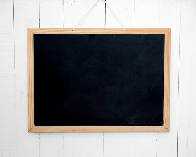 Blank wooden slate hanging on white wall Free Photo