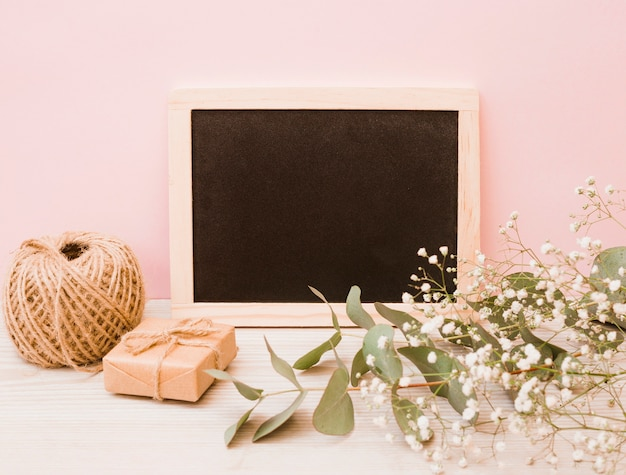 Blank wooden slate with spool; gift box and baby's-breath flowers on wooden desk against pink background Free Photo