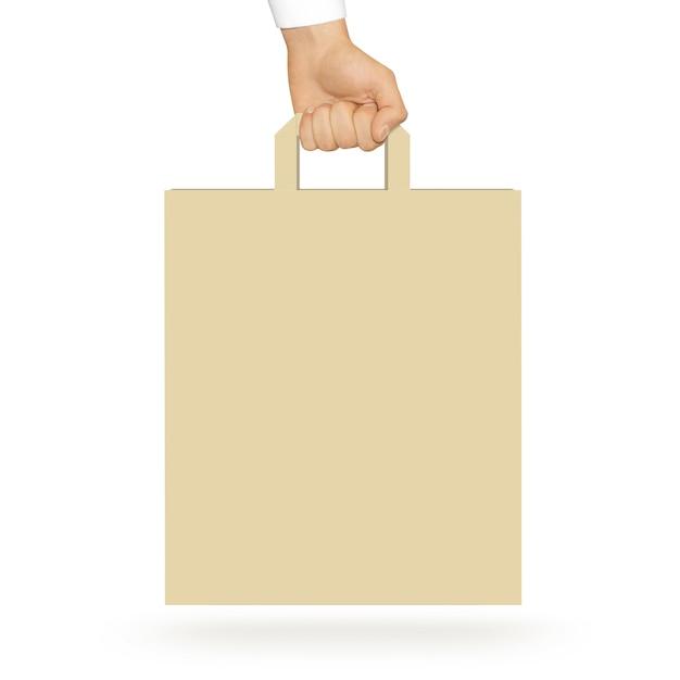 Blank yellow paper bag holding in hand Premium Photo