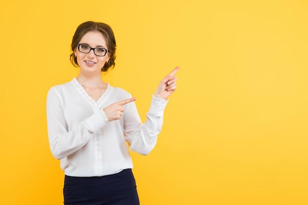 黄色のblankareaに自信を持って美しい若い笑顔幸せなビジネスの女性ショーの肖像画 Premium写真