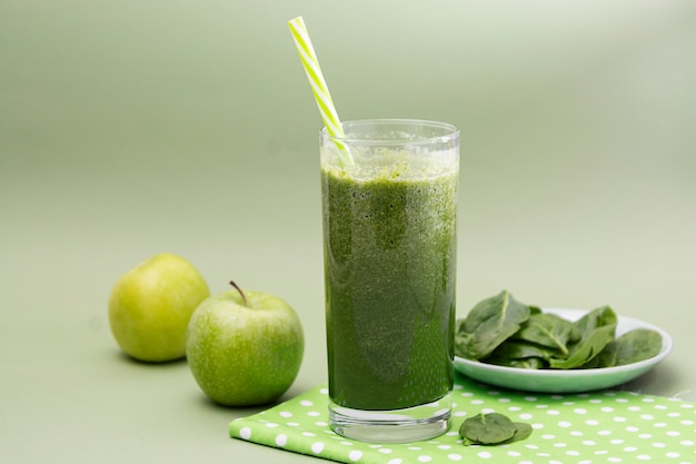 Blended green smoothie glass selective focus, green background. healthy food. Premium Photo