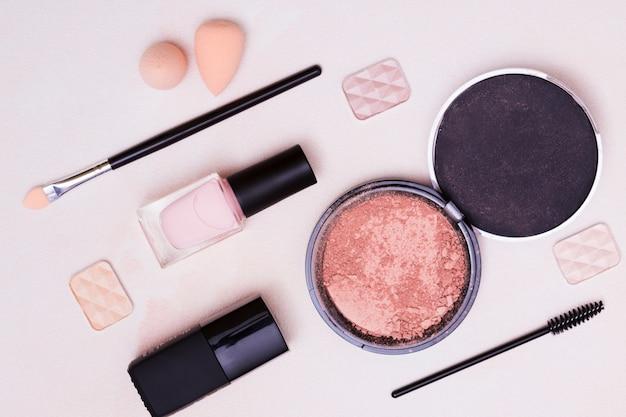 Blender sponge; makeup brush; eyeshadow; compact face powder on pink background Free Photo