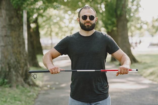 盲目の男。障害者、障害者、日常生活。都市公園の階段を降りて、杖を持つ視覚障害者。 無料写真