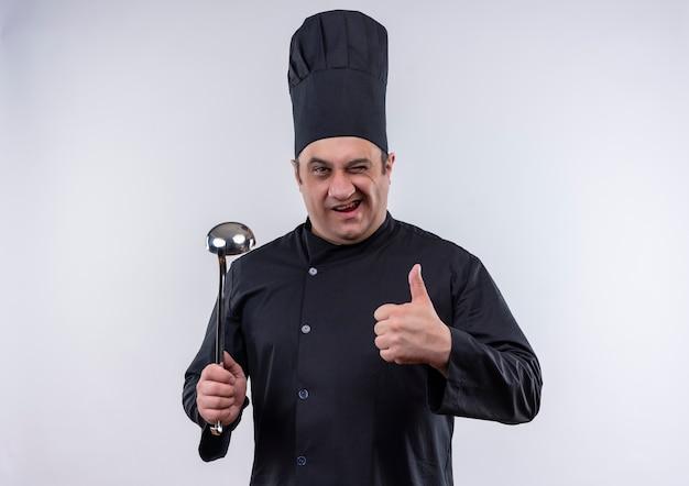 Моргнул мужчина-повар средних лет в униформе шеф-повара, держа большой палец лопаткой на изолированной белой стене Бесплатные Фотографии