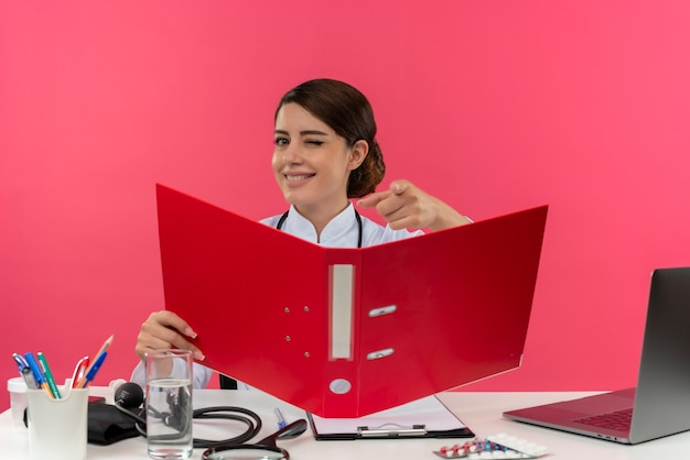 Blinked smiling young female doctor wearing medical robe with stethoscope sitting at desk work on computer with medical tools holding folder showing you gesture on pink wall with copy space Free Photo