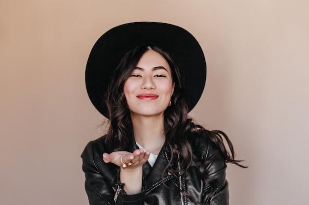 Блаженная азиатская женщина в шляпе показывать на бежевом фоне. студия выстрел романтичной курчавой японки в кожаной куртке. Бесплатные Фотографии