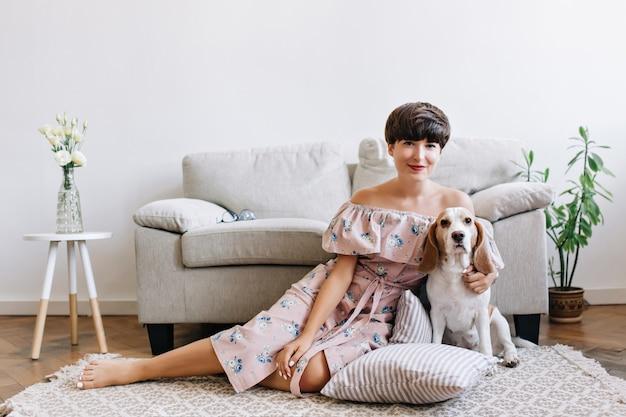 かわいい服を着た至福のブルネットの少女は、子犬と一緒に灰色のソファの前のカーペットの上に座っています 無料写真