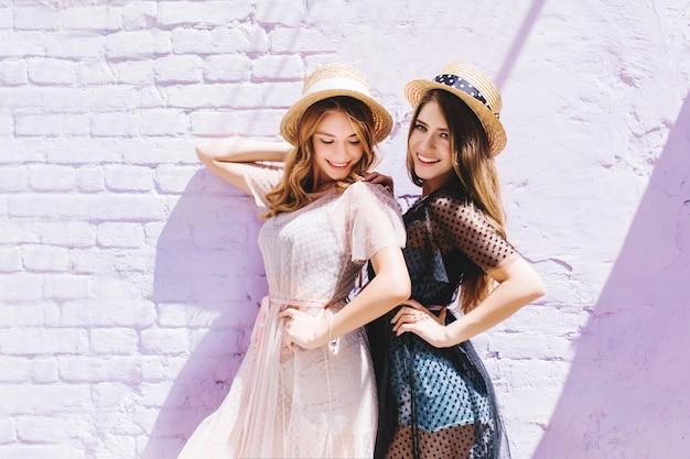 Блаженная кудрявая девушка в легком винтажном платье смотрит вниз, позируя рядом с очаровательной сестрой Бесплатные Фотографии
