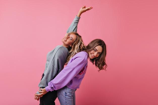 Блаженные подруги в уличной одежде, взявшись за руки на розовом. позитивные кавказские дамы танцуют с удовольствием. Бесплатные Фотографии