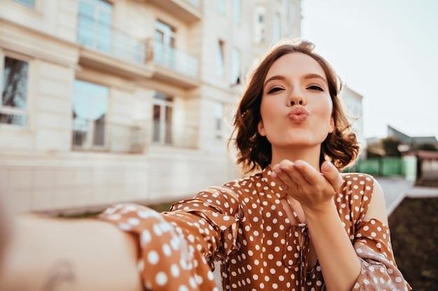 路上で自分撮りを作る古着の至福の少女。空気のキスを送る茶色の服を着たゴージャスな白人女性 無料写真