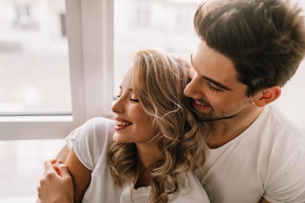 Блаженный парень обнимает подругу утром. крытый портрет расслабленной блондинки, расслабляющейся с парнем. Бесплатные Фотографии