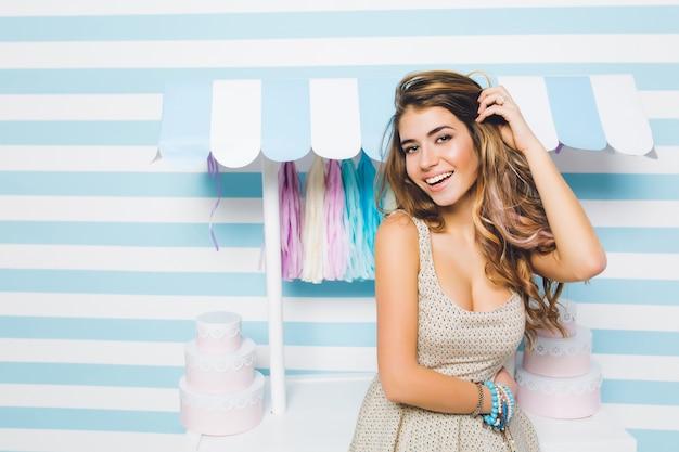 Блаженная длинноволосая девушка в модном винтажном платье позирует с красивой улыбкой перед магазином сладостей. великолепная молодая женщина с блестящими волосами, стоящая рядом с прилавком конфет на милой полосатой стене. Бесплатные Фотографии