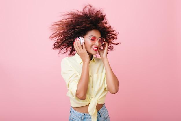 Beata mulatta in camicia di cotone gialla che scherza nella stanza rosa. ragazza nera soddisfatta con l'acconciatura marrone riccia che tocca le cuffie bianche e che ride. Foto Gratuite