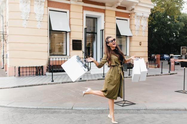 Блаженная шопоголическая женщина танцует на улице с улыбкой Бесплатные Фотографии