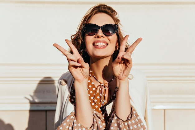 Blissful short-haired girl laughing in sunny day. portrait of carefree brunette woman in black sunglasses posing with peace sign. Free Photo