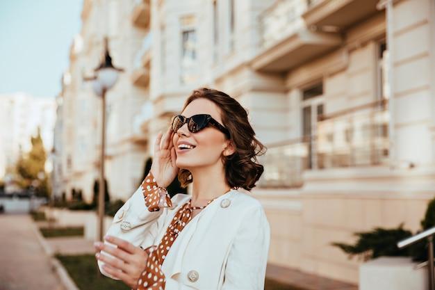 大きな古い建物の近くでポーズをとる至福のスタイリッシュな女性。秋の日にぼやけた街のbakgroundに立っている洗練された白人の女の子。 無料写真