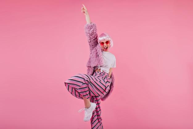Блаженная женщина в полосатых штанах и розовом парике смеется во время фотосессии. уверенная барышня в солнечных очках и пушистой куртке, смешные танцы Бесплатные Фотографии