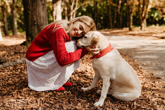 Ragazza bionda beatamente felice che sorride vicino al suo cane. bella donna che si sente felice con l'amato animale domestico. Foto Gratuite