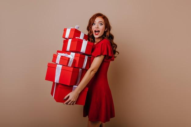 Веселая именинница в платье позирует с подарками. радостная молодая женская модель, держащая новогодние подарки. Бесплатные Фотографии