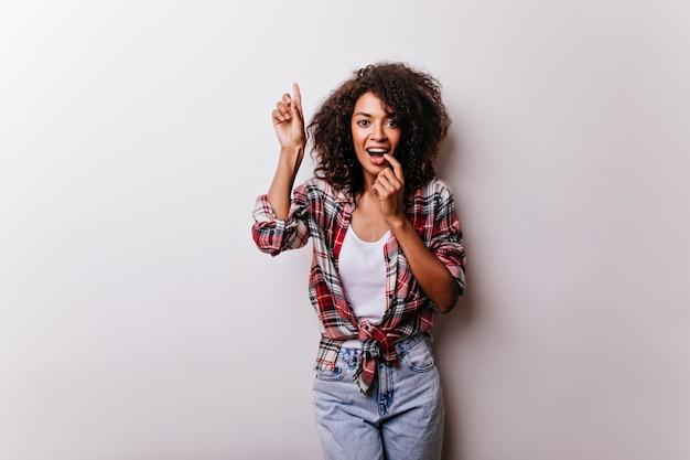 Веселая черная девушка с вьющейся прической, смешно позирует на белом. африканская красивая дама стоит с нежной улыбкой. Бесплатные Фотографии