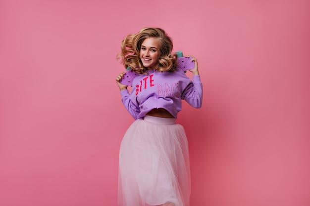Беспечная блондинка в длинной юбке, держащей скейтборд. крытый портрет очаровательной женской модели с лонгбордом. Бесплатные Фотографии