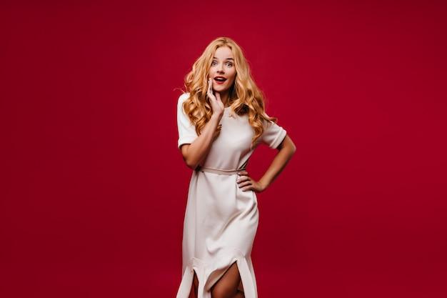 Беспечная гламурная девушка в белом платье, стоящем на красной стене. беззаботная светловолосая женщина, выражая изумление. Бесплатные Фотографии