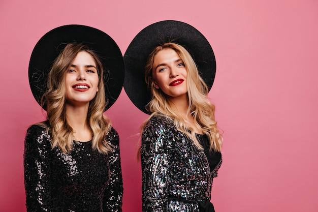 Donne bianche allegre in cappelli che posano sul muro roseo. ritratto dell'interno di ragazze caucasiche fiduciose con accessori glamour. Foto Gratuite