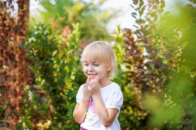 緑豊かな公園で屋外の小学校時代の幸せな小さなblobde女の子のクローズアップの肖像画 Premium写真