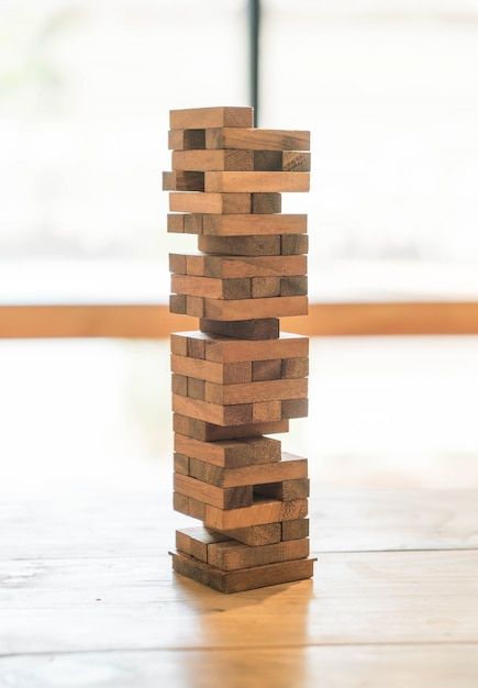 Blocks wood game (jenga) on wooden table Free Photo