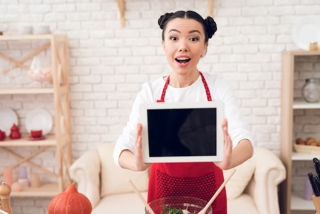 Blogger girl holds up blank tablet to camera Premium Photo