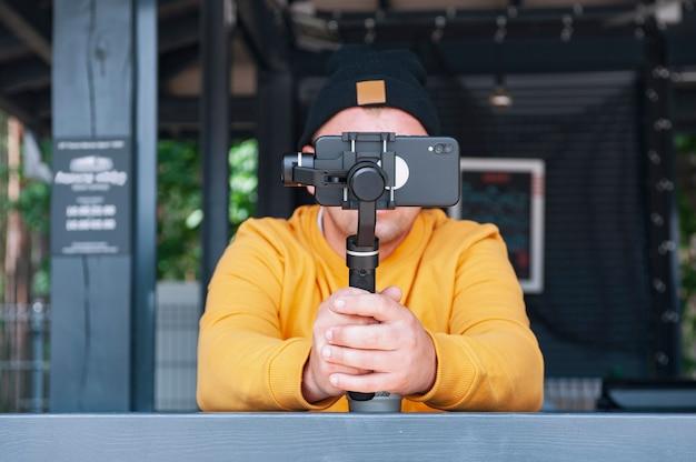 コーヒーのブロガーは、手動カメラスタビライザーを備えたスマートフォンでビデオを撮影します。 Premium写真