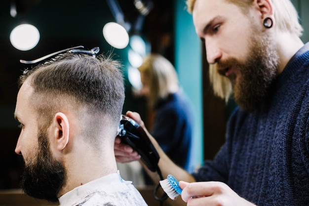 Blond bearded barder makes fade on man's hair attentively Photo