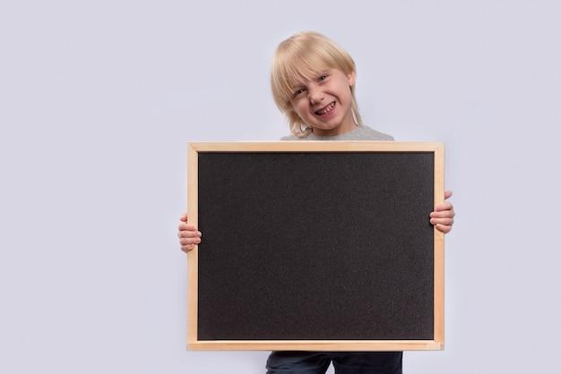黒板を押しながら笑顔の金髪の少年。スペースをコピーします。テンプレート。モックアップ。 Premium写真