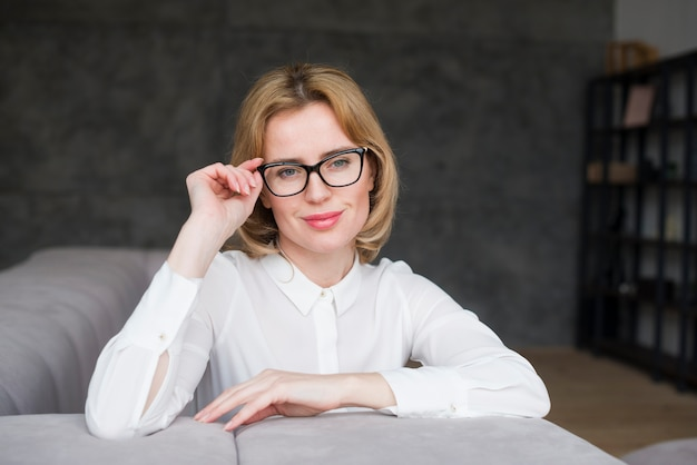 Blond business woman in glasses sitting on couch Free Photo