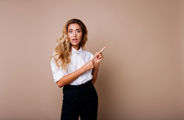 Blond business woman pointing up and looking on beige wall. wearing stylish workwear. copy space fo text. surprise face. Free Photo