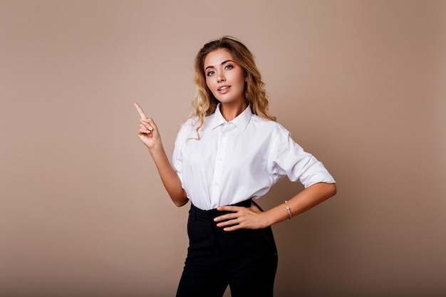 Blond business woman pointing up and looking on beige wall. wearing stylish workwear. copy space fo text. Free Photo
