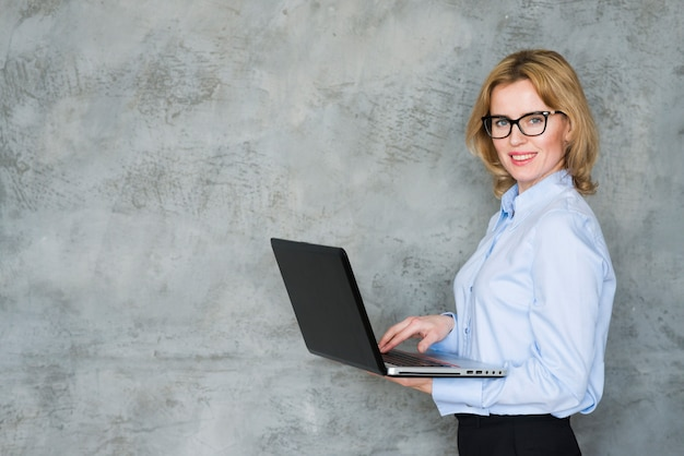 Blond business woman using laptop Free Photo