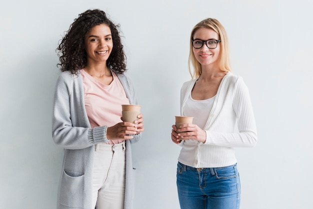 Blond and ethnic coworkers with coffee cups Free Photo